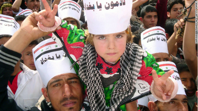 An Iraqi boy wears a placard reading 'Baghdad we are coming' during rally on March 1, 2013 in Hawijah, near Kirkuk (Source: CNN)