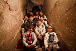 Children pose for a group portrait in the hallway of a house shared by four families.  UNICEF