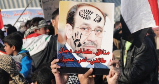 "Iraqi Sunni protestors hold up a portrait of Prime Minister Nuri al-Maliki with slogans reading in Arabic, ""liar...sectarian, thief, collaborator"" during a protest against him on the main highway to Syria and Jordan near Ramadi, Anbar's provincial capital west of Baghdad, on January 4, 2012. Thousands of Sunnis demonstrated across Iraq on Friday, in the latest of nearly two weeks of rallies criticising the country's premier and demanding the release of prisoners they say are wrongfully held. AFP PHOTO / AZHER SHALLAL        (Photo credit should read AZHER SHALLAL/AFP/Getty Images)"