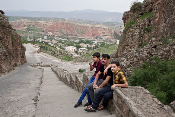 Three young men from Anbar province sit on a wall that overlooks the town of Shaqlawa.