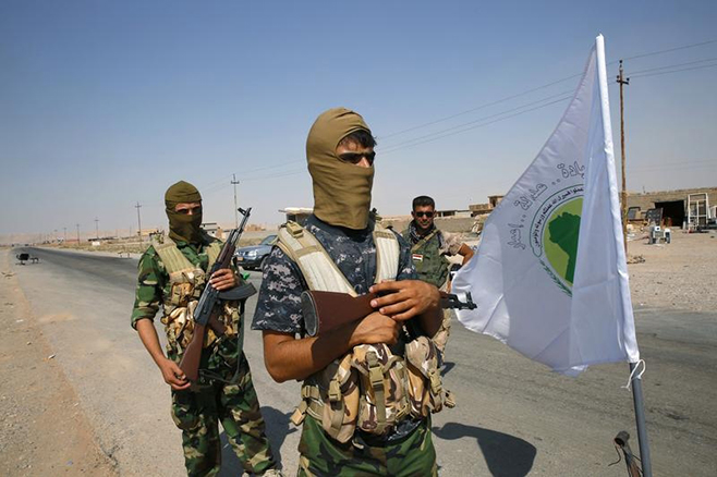 Fighters from the Shi'ite Badr Brigade militia stand near their flag as they guard at a checkpoint outside the town of Sulaiman Pek