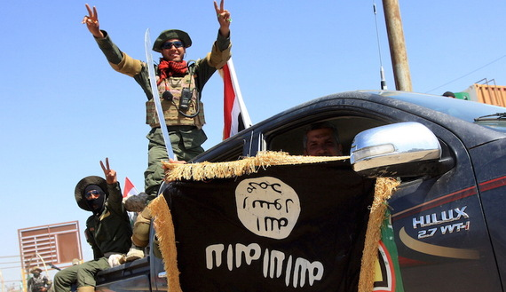 Shi'ite paramilitary fighters hold an Islamist State flag which they pulled down during victory celebrations after returning from Tikrit in Kerbala