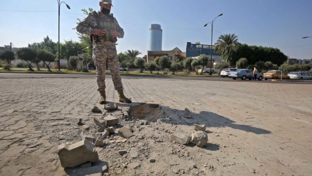 A member of the Iraqi security forces inspects the damage outside Zawraa park in Baghdad, after a volley of rockets slammed into the Iraqi capital breaking a monthlong truce on attacks against the US Embassy, Iraq, Nov. 18, 2020.